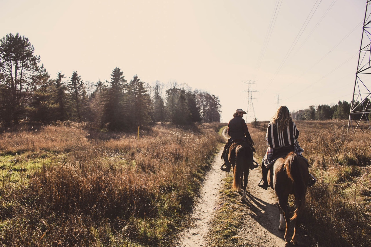 two people on horseback on a trail