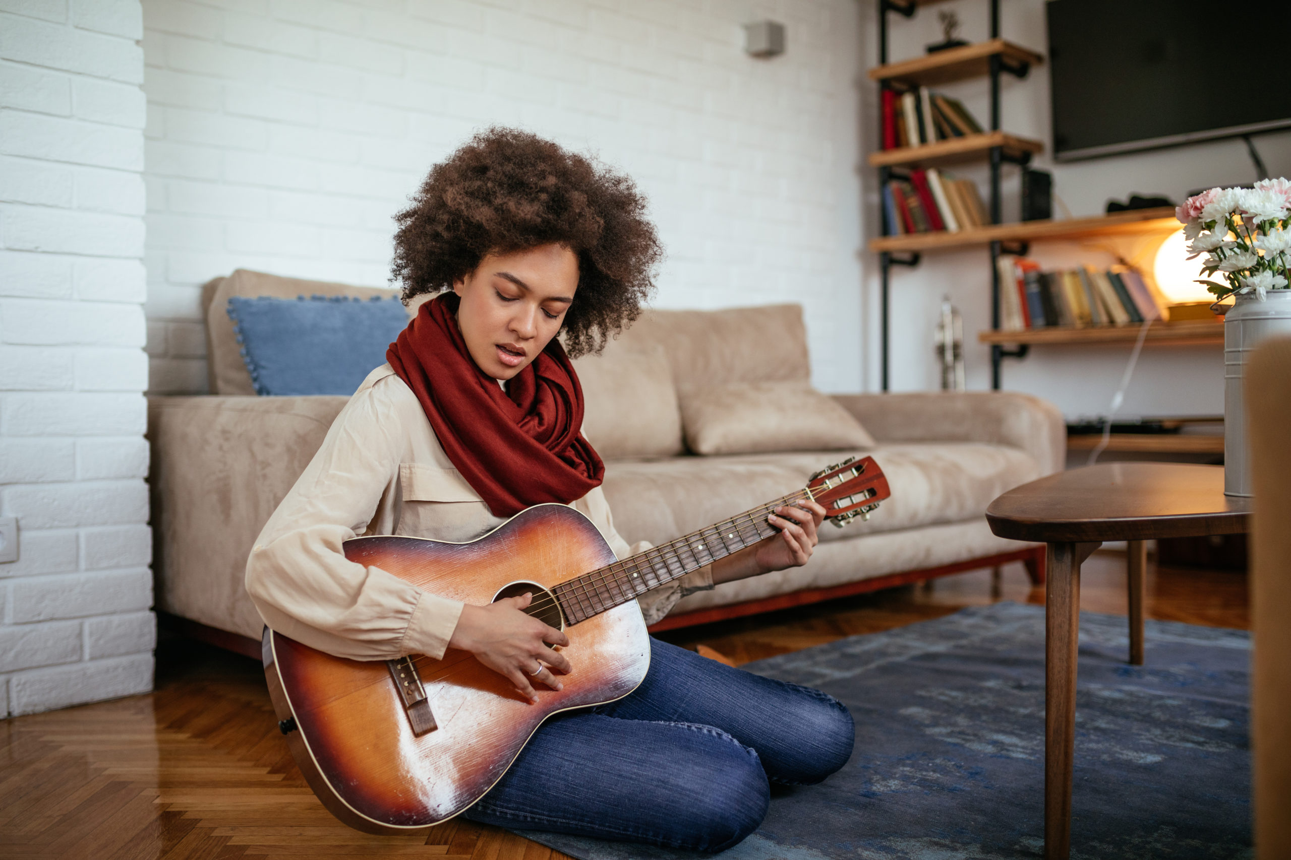 woman playing a guitar at home.