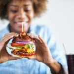 woman eating burger from Clarksburg eateries